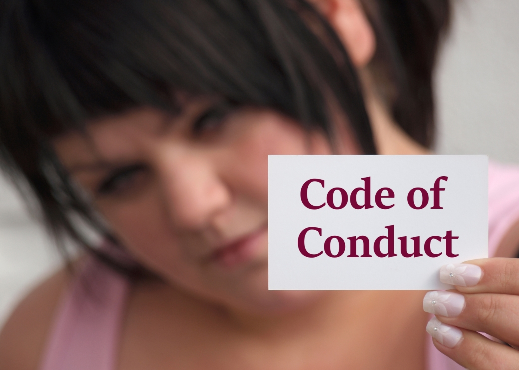 lady holding a card with words Code of Conduct written on it